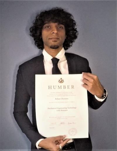 Rohan Chamroo is standing in front of a grey background wearing a suit, smiling and holding his credential
