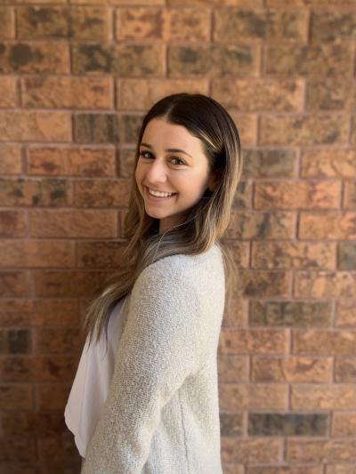 Julia Campa stands in front of a brick wall, smiling at the camera over her shoulder, wearing a grey sweater