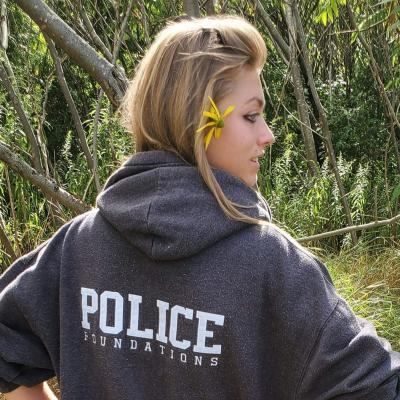 """Alexandra Kaske has her back to the camera, looking over her right shoulder. Her sweatshirt says """"POLICE foundations."""""""