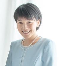 Kayoko Ochi smiles at the camera, wearing a light blue sweater