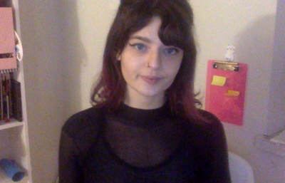 Thais Grandisola smirks at a web camera. She is wearing a black shirt and has medium-length brown hair