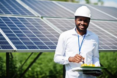 A man smiles in front of a giant solar panel with a white hard hat and white shirt, holding a clipboard