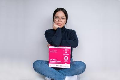 Oat Canada co-founder Eloise Ambursley sits cross legged with a pink box of oat milk on her lap