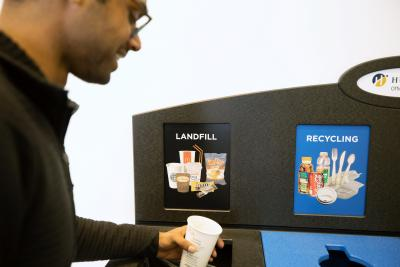 Devon Fernandes tries out the new waste bin at the North campus LRC