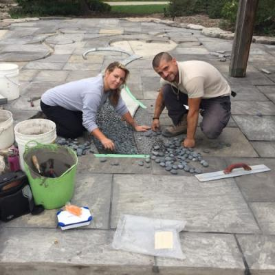 Two people are hunched over, working on a mosaic tile on the cobblestoned ground