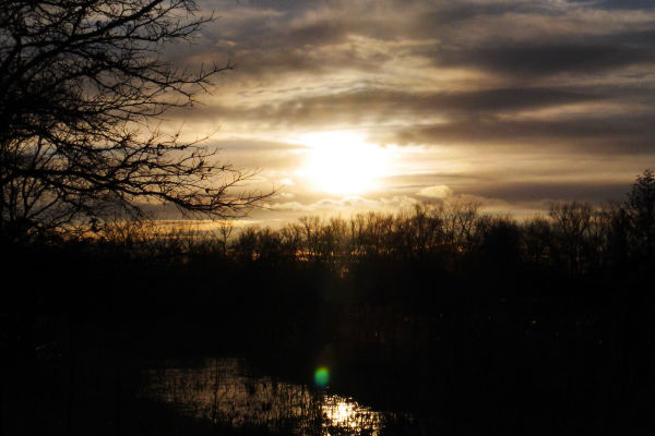 The sun sets over a pond and meadow